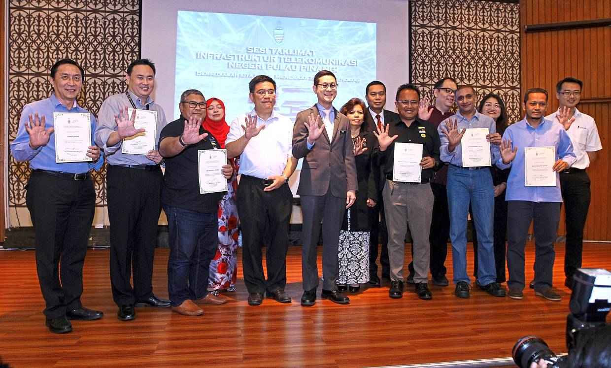 Zairil (with white tie), Bukit Bendera MP Wong Hon Wai (on his right) and several state assemblymen with the telco representatives after presenting them with certificates at the event in Komtar, George Town.