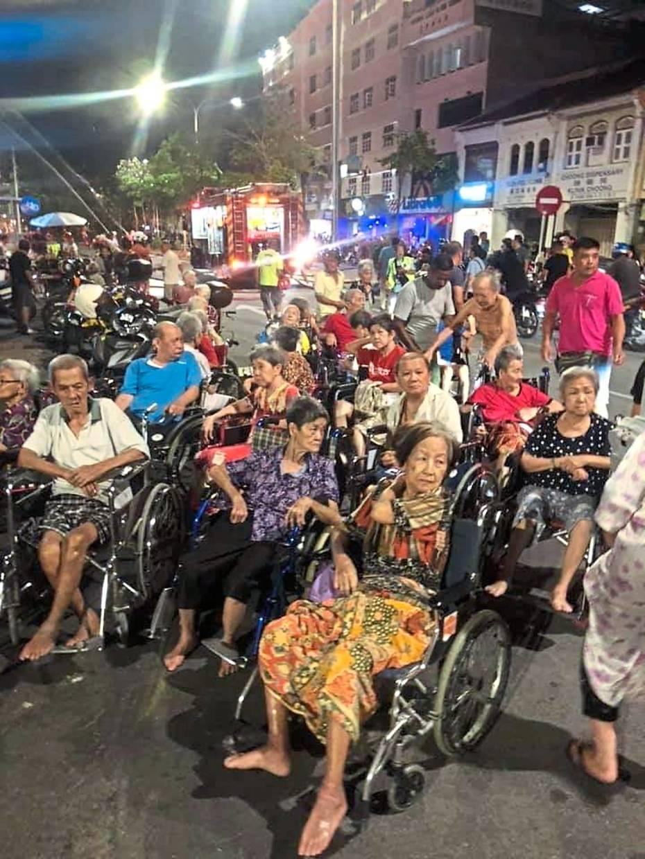Helpless: Volunteers moving elderly folk in their wheelchairs to safety.