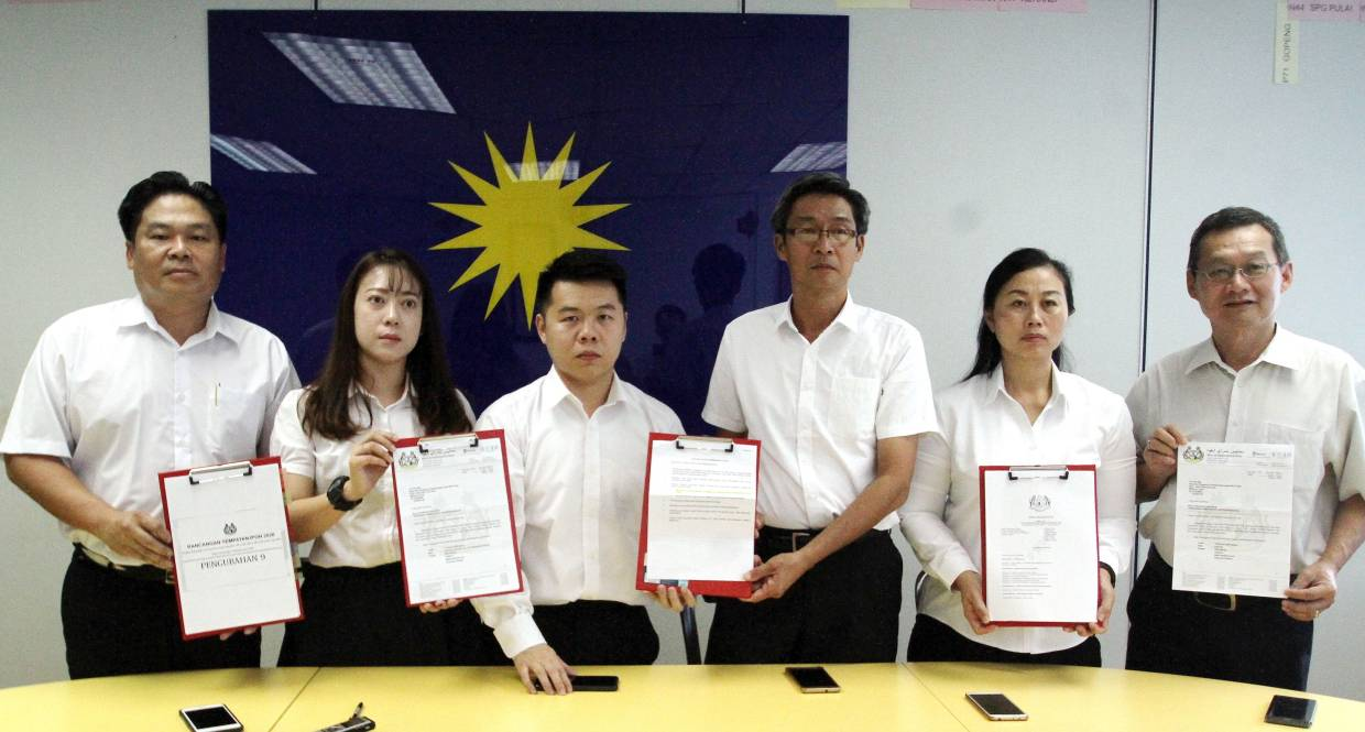 Perak MCA Complaint Bureau Chief Low Guo Nan (4th right) showing the clause act on the five issues over protest on changes in land status by the Ipoh City Council.