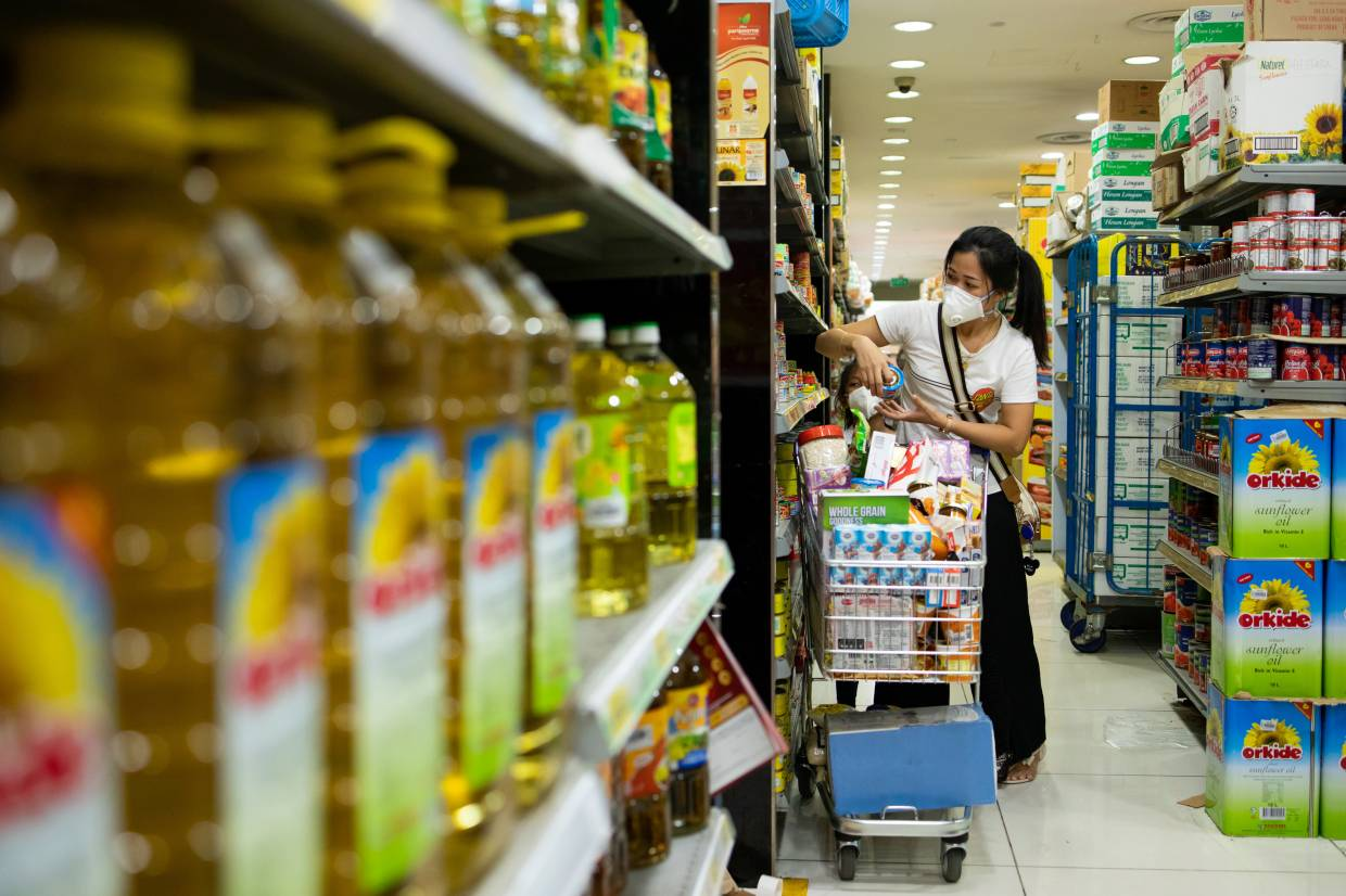 A customer wearing a protective mask while browsing goods inside a supermarket in Singapore. Singapore authorities urged residents to relax on their shopping sprees that have emptied supermarket shelves, saying supplies aren't under threat even as response efforts to battle the coronavirus outbreak have escalated. — Bloomberg