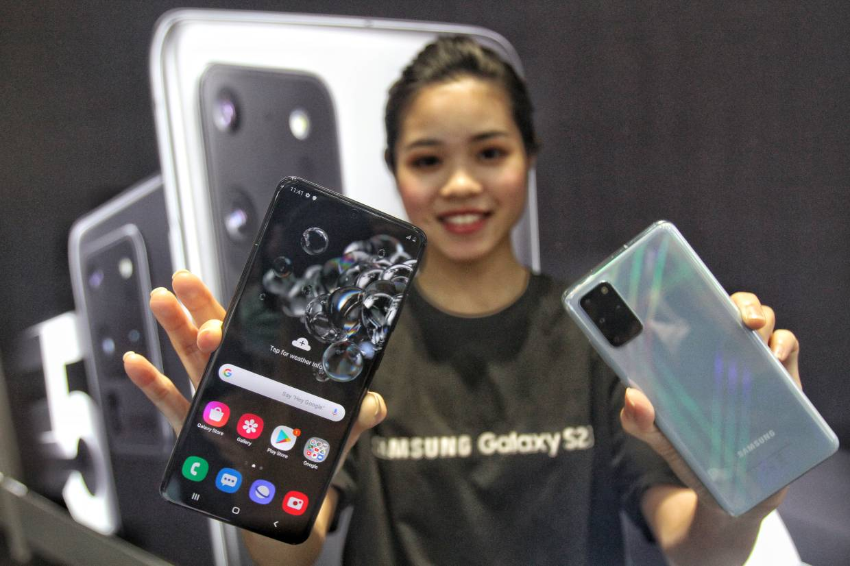 A model showing off two of the three new smartphones from Samsung's latest flagship S20 series at its launch in Kuala Lumpur. — SAM THAM/The Star