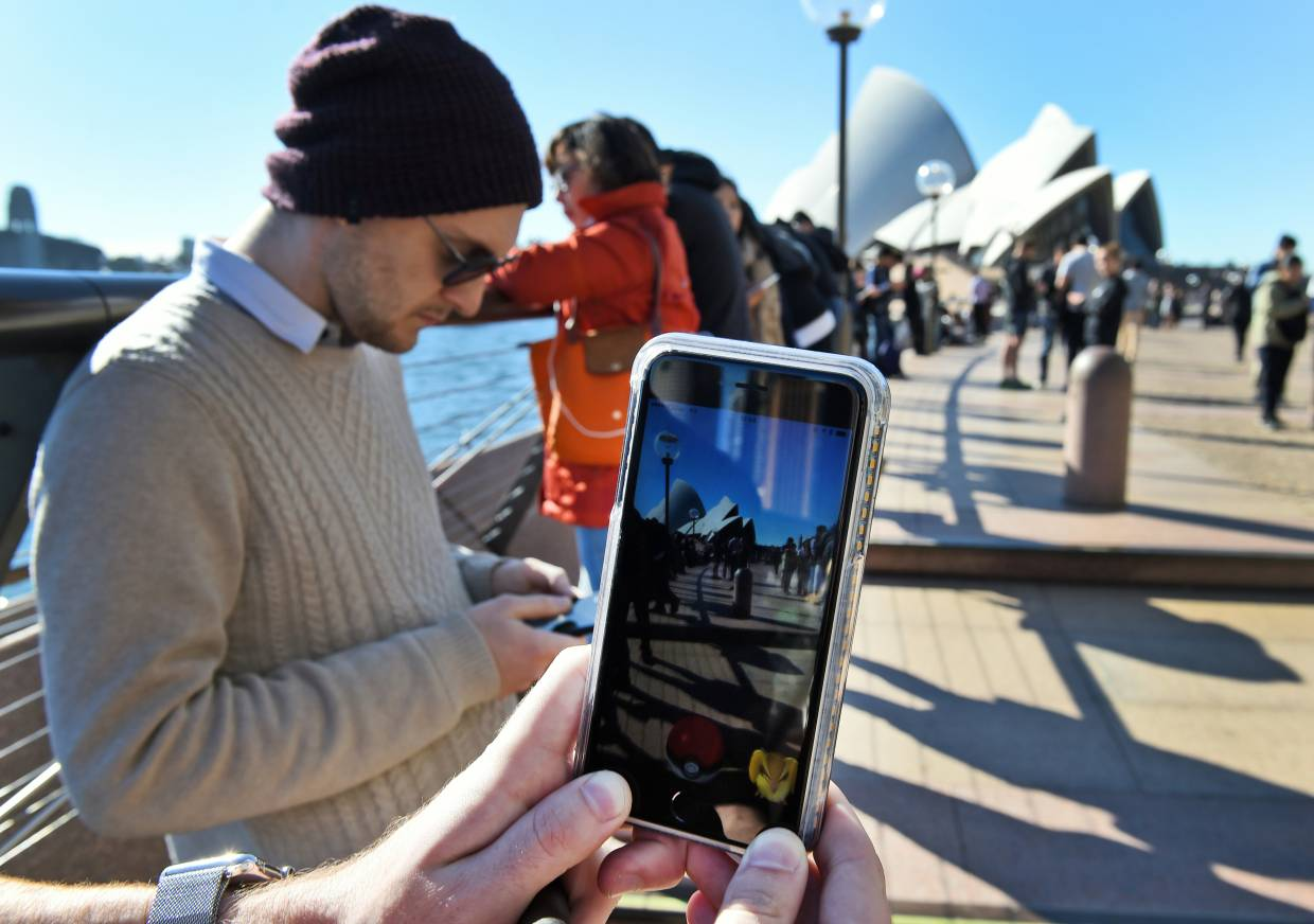 Some gamers combine gaming in their travel plans, playing the game while enjoying tourist attractions (such as the Sydney Opera House seen in the background). — AFP