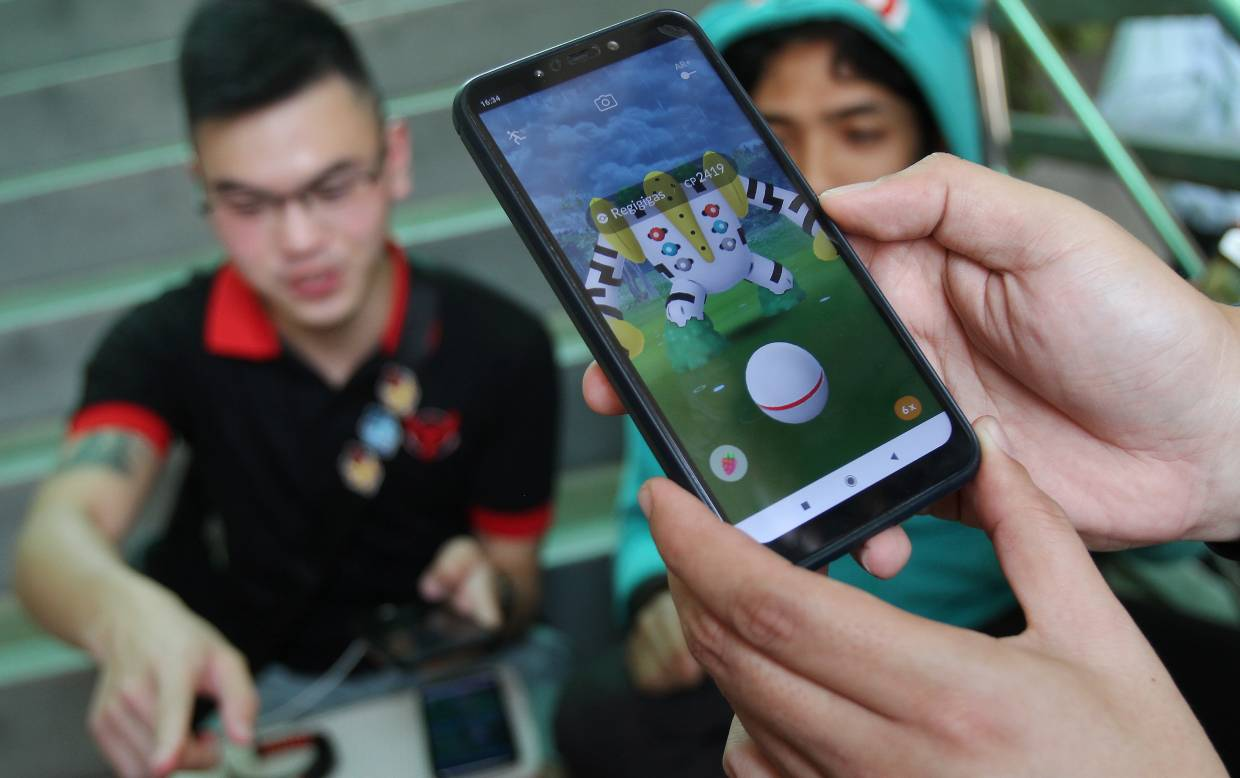 Augmented reality gaming enthusiasts gather for events in the real world (such as raids in the case of Pokemon Go). — MUHAMAD SHAHRIL ROSLI/The Star