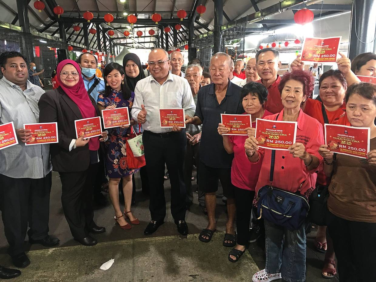 Sayuthi (front centre in white shirt) with the recipients of MBPJ's cash donation and assemblymen from Petaling Jaya.