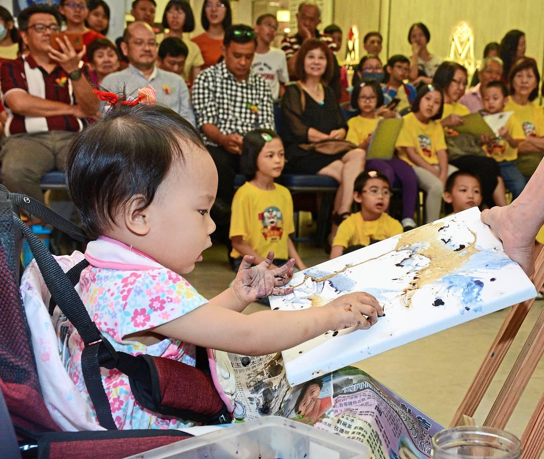 一岁的克尔维在现场绘画期间在一块空白的画布上创作了一个抽象的作品