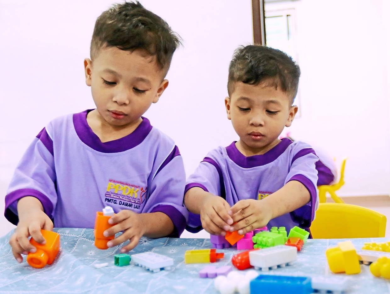 五年多动症的老年双胞胎专注于一项活动。