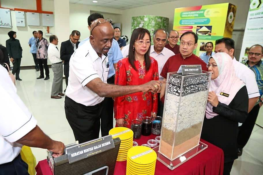 Kok (in red) being briefed on CMB and how it is used in building roads by MRB chairman Datuk Sankara Nair.