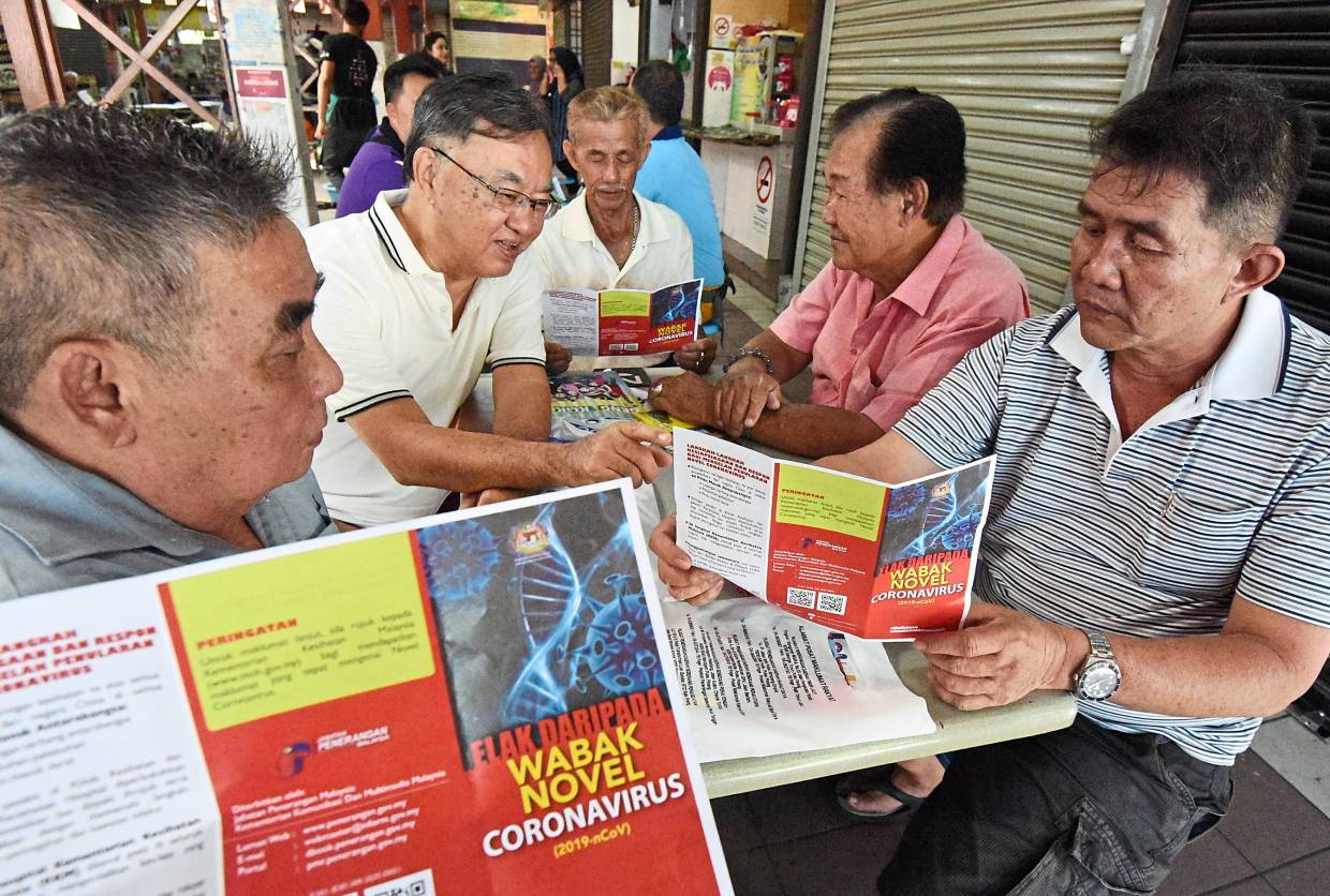 Customers at a food court in Lorong Kulit reading the pamphlets.