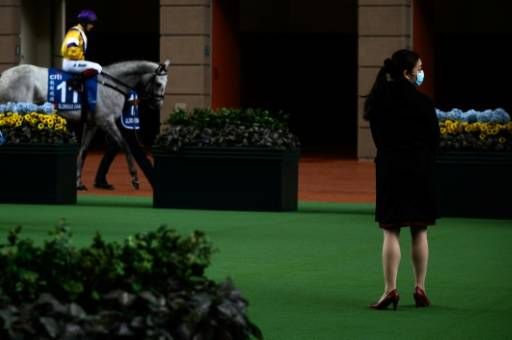A Hong Kong Jockey Club employee wears a face mask in the parade ring at an empty Sha Tin racecourse on Hong Kong Gold Cup day.