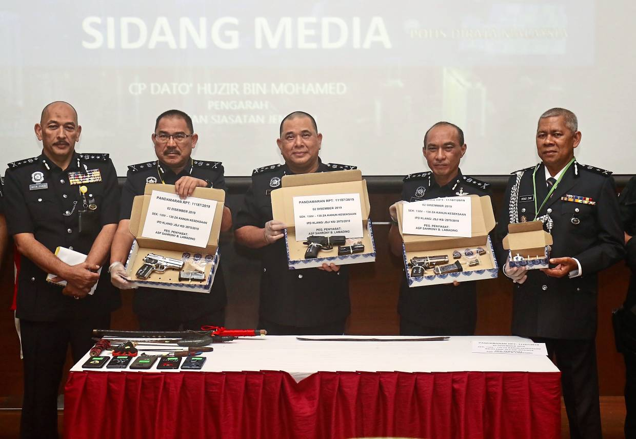 Safer streets: Comm Huzir (centre) and fellow officers showing the media some of the items seized following the arrest of AYT99 gang members in Bukit Aman.
