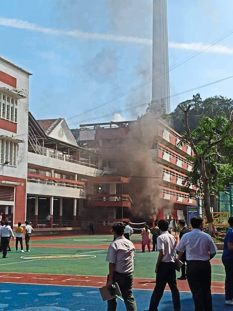 Keeping their distance: Students and teachers in the designated safe zone at the school's basketball court watching the smoke coming out from the Arts Block.