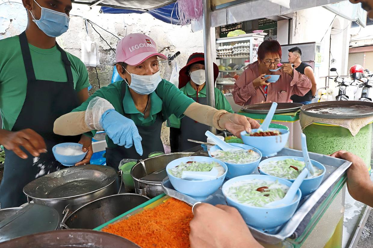 Taking precaution: Staff of Penang Road Famous Teochew Chendul wearing face masks  as they serve customer at their stall in Lebuh Keng Kwee, Penang.