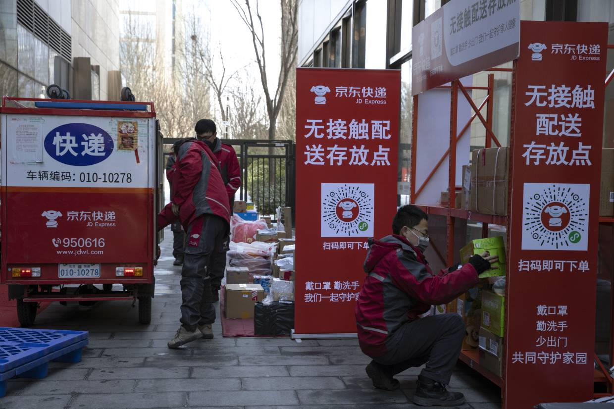 Delivery workers for Chinese e-commerce giant JD.com set up a temporary No Contact parcel collection point outside an apartment complex in Beijing, China.