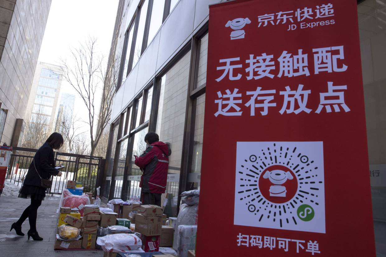 A resident looks for her parcel near a temporary No Contact parcel collection point for Chinese e-commerce giant JD.com outside an apartment complex in Beijing, China.