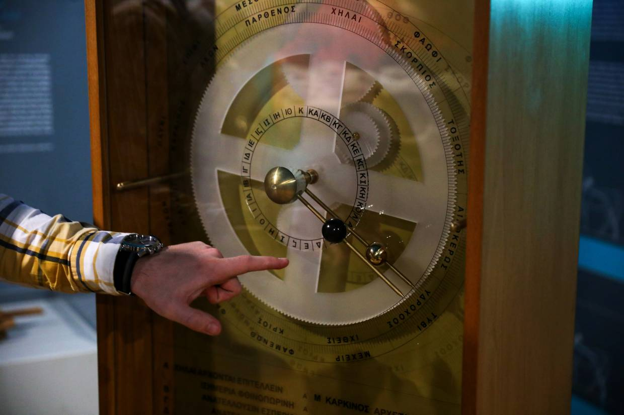 A Kotsanas Museum of Ancient Greek Technology employee presents a replica of the ancient Antikythera Mechanism, in Athens, Greece.