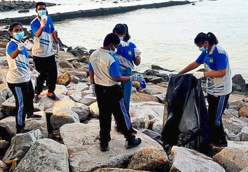 The students putting the rubbish into a large garbage bag during the beach cleanup.