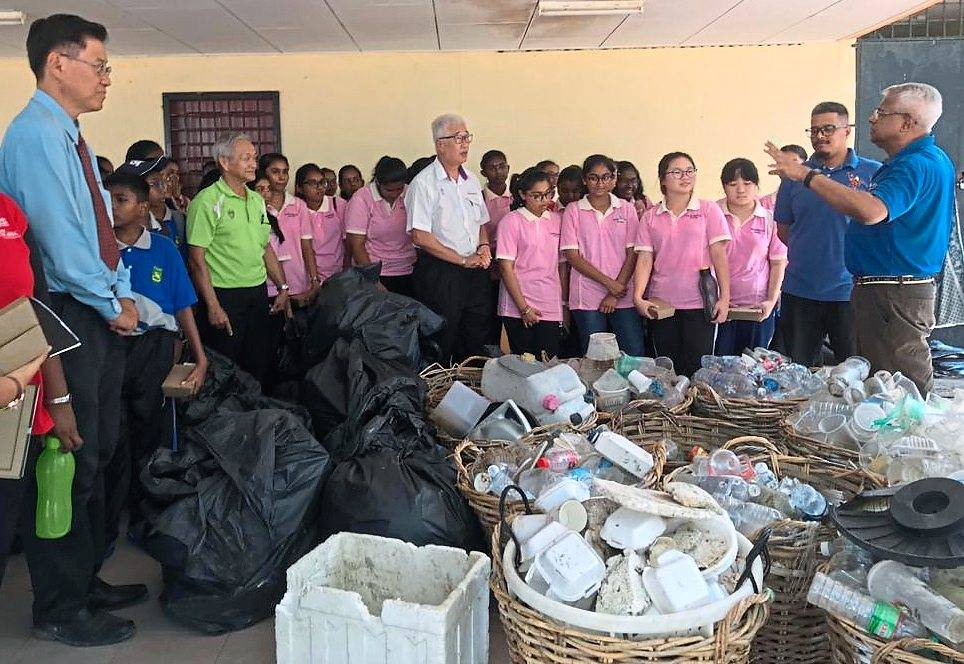 Jeyabalan (right) briefing Phee (in white shirt) about their collection of trash from the beach in the presence of the students, Tan (left) and Chew (green T-shirt).
