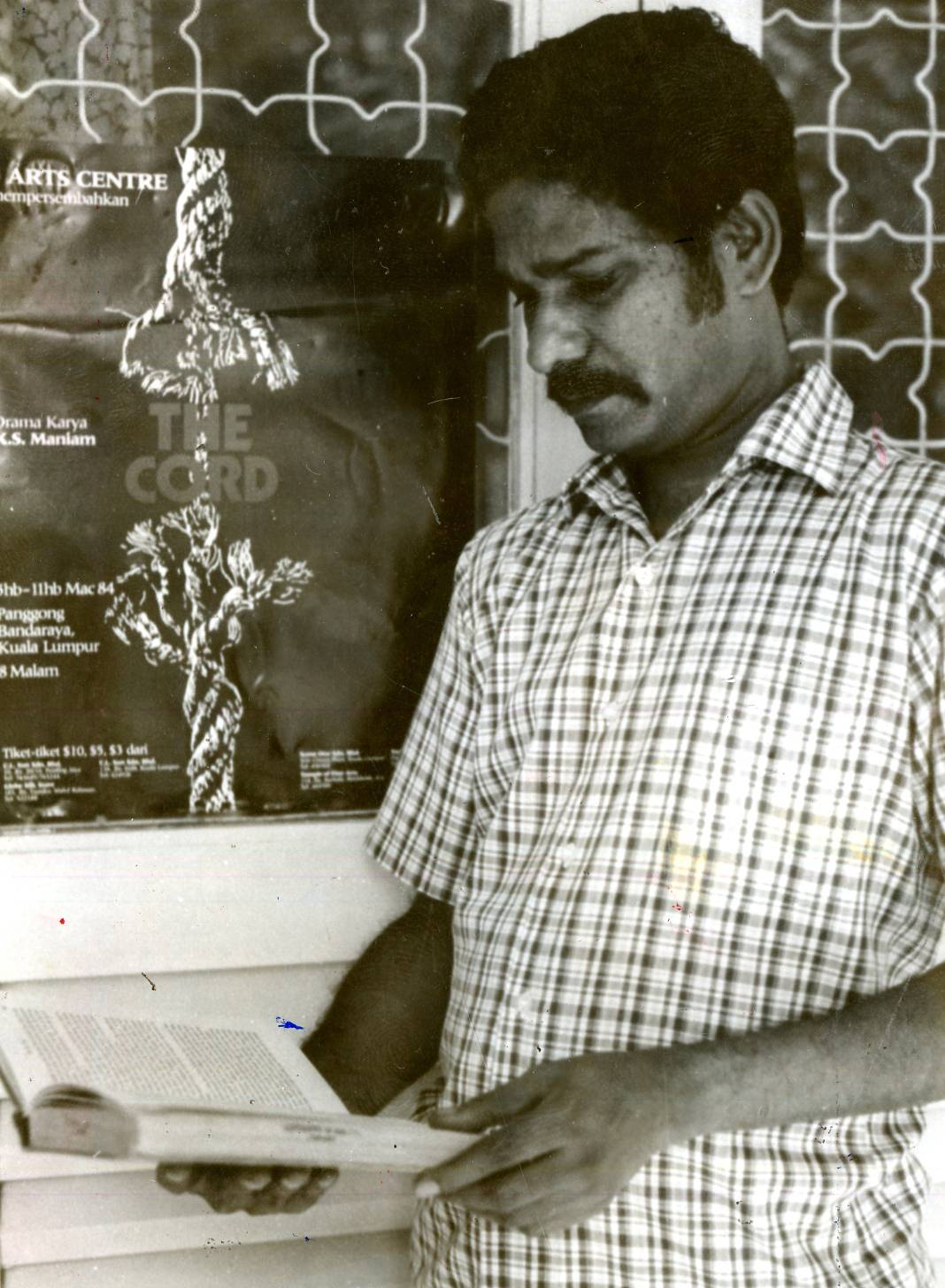 Maniam, as a playwright and founding member of Five Arts Centre, standing before a publicity poster of his play 'The Cord' in 1984. Photo: Filepic