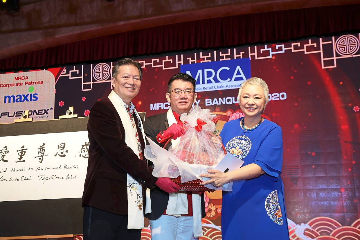 Chua (left) presenting a token of appreciation to Cheng (right).