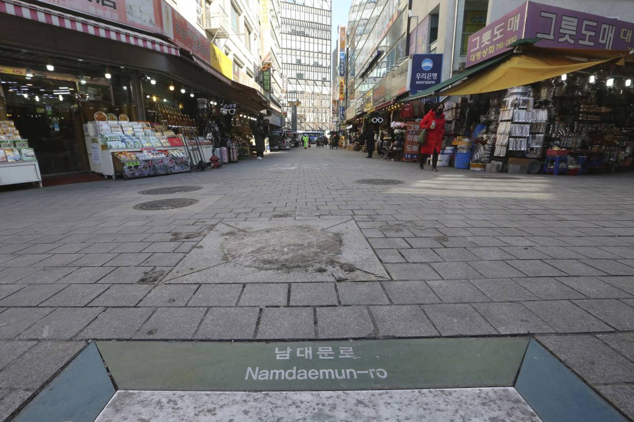 A woman wearing a face mask walks on the almost empty Namdaemun Market street in Seoul, South Korea.