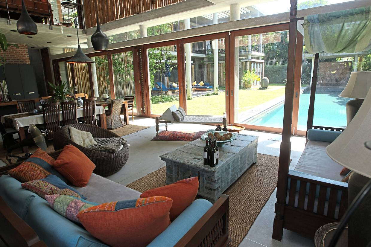 The living room looks out to the pool and covered terrace through glass doors which, when opened up, blends the indoors with the outdoors.