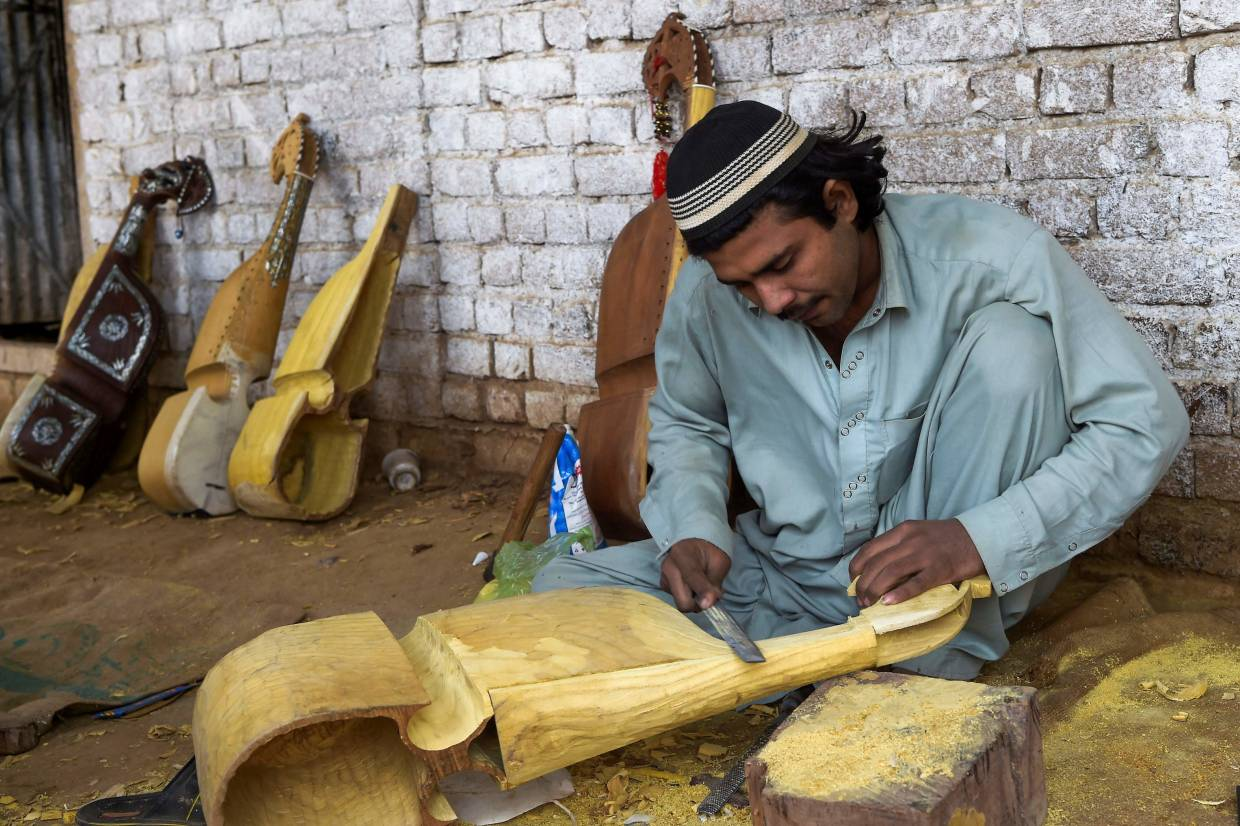 A worker makes a traditional rabab musical instrument in a workplace on the outskirts of Peshawar. Photo: AFP