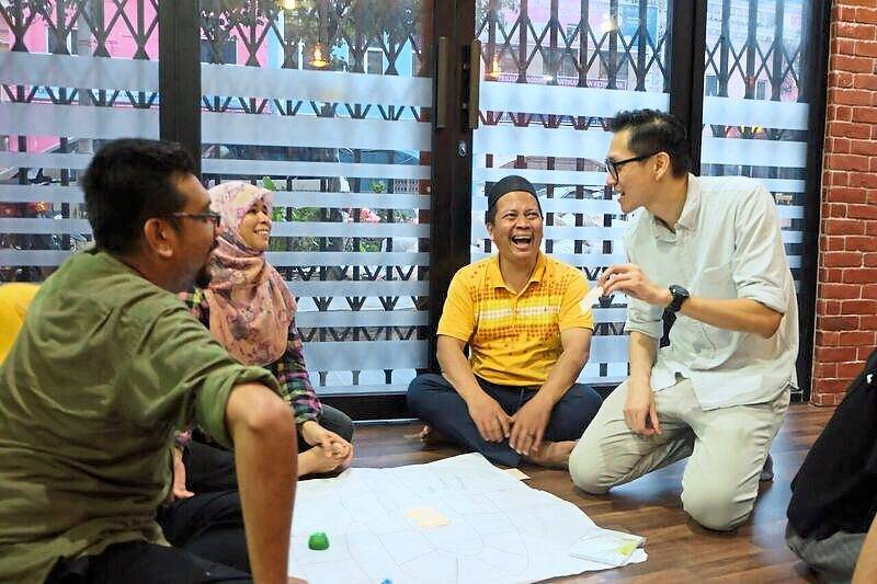 Financial management trainer Chun Wah Hoo (right) having a light moment with his students.