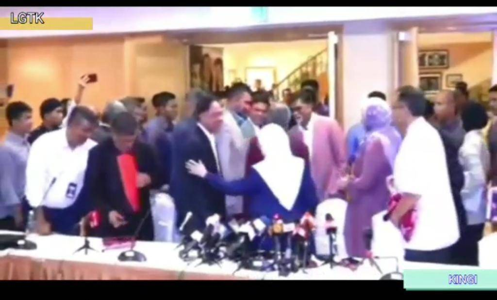 Dr Wan Azizah (back to camera, white hijab) seemingly consoling Anwar with a pat on his arm at the end of the press conference. — Screen capture from StarTV video