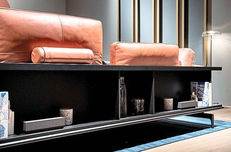The back and armrests of the Liv sofa system by Rolf Benz are also shelves for books or accessories.