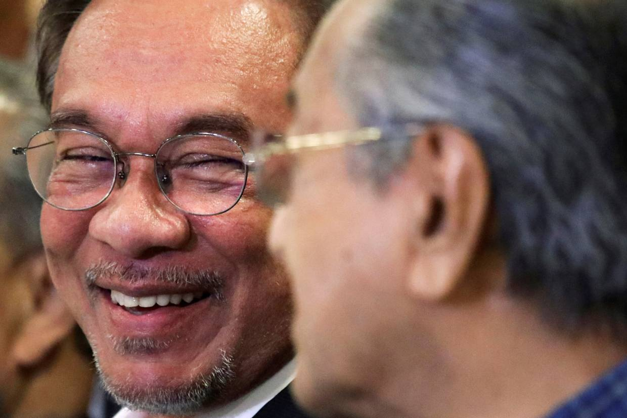 A file picture of Anwar speaking to Dr Mahathir at a news conference.