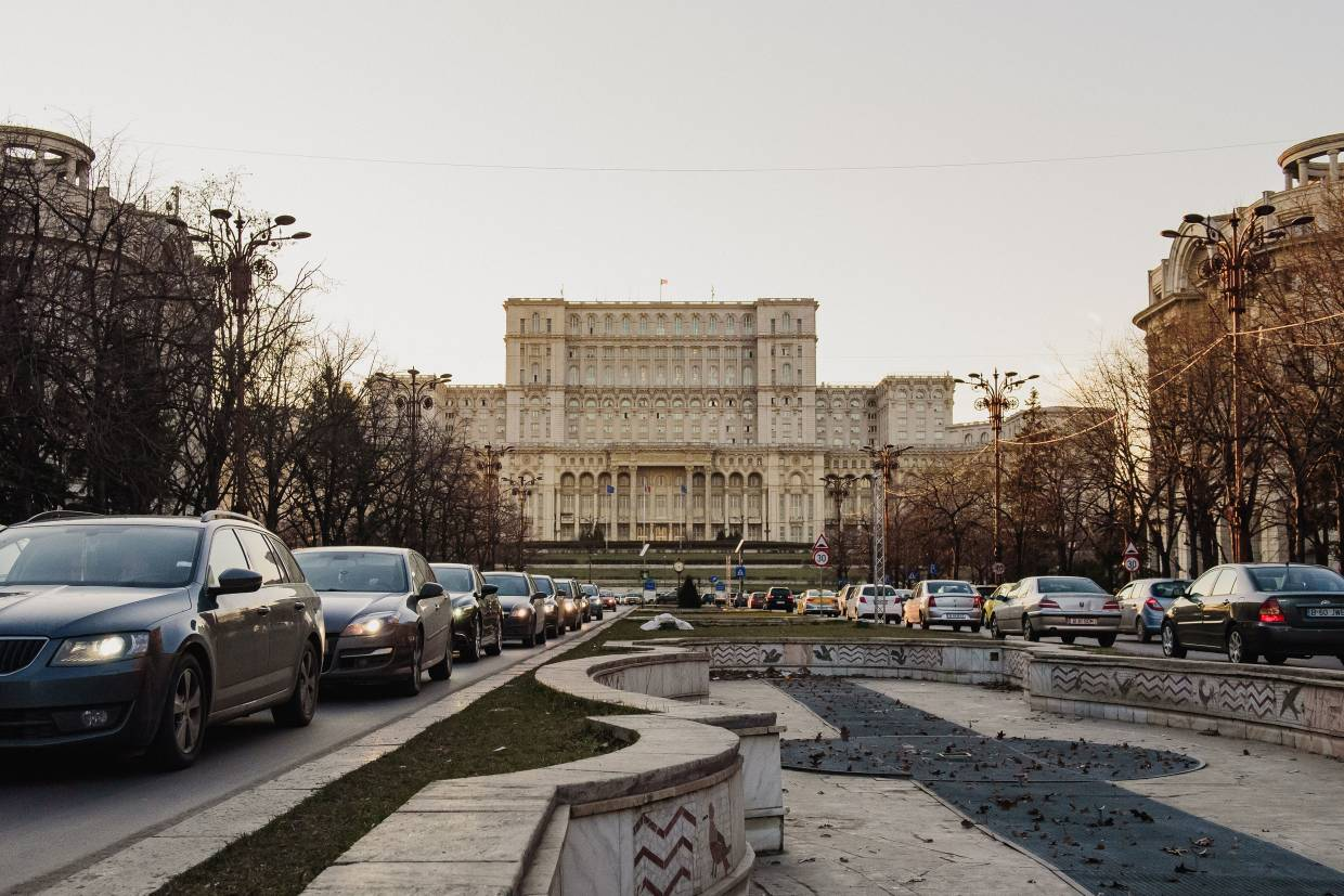 Automobiles idle in a traffic jam on Boulevard Unirii near the Palace of the Parliament building in Bucharest, Romania.