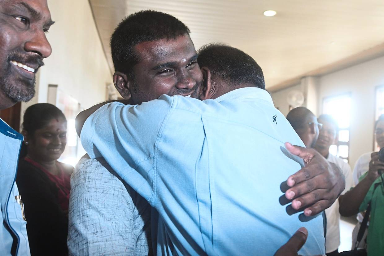 Huge relief: Saminathan being hugged after his acquittal at the High Court in Kuala Lumpur. (Bottom) Pumugan smiling while walking out of court a free man. — Bernama