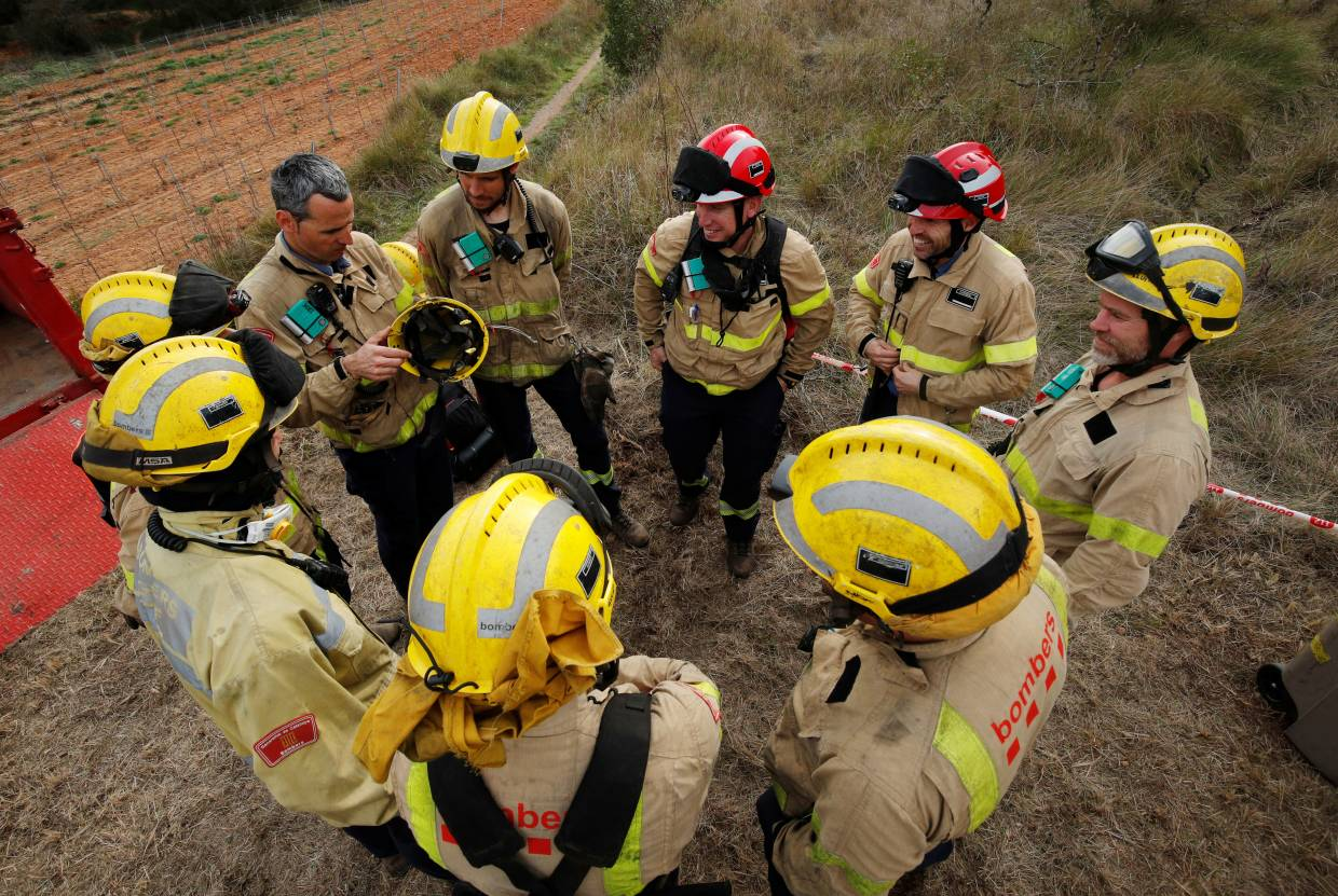 A group of firefighters do a meeting wearing a Prometeo monitoring device (by IBM) during prescribed burn of the forest in Olivella, south of Barcelona, Spain.