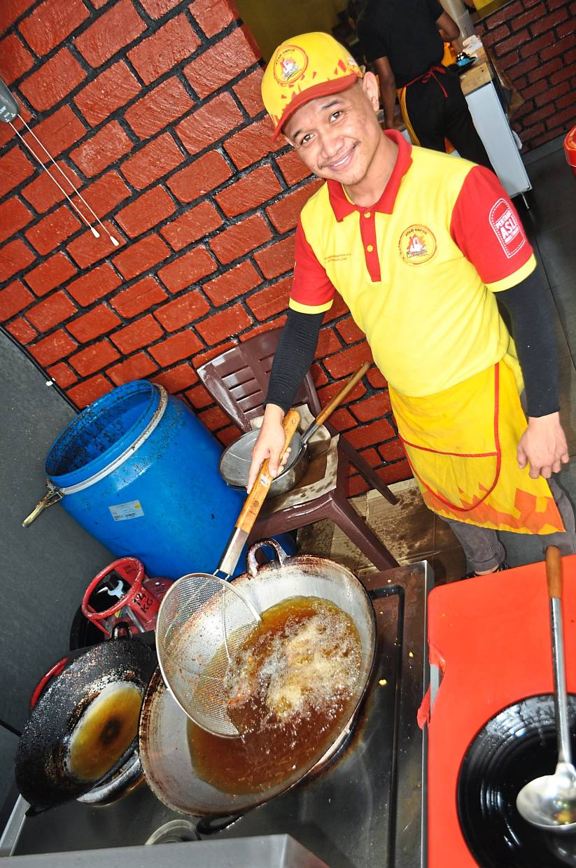 This worker at a restaurant in Putrajaya will empty the used cooking oil into a drum behind him. This will then be collected by waste contractors.