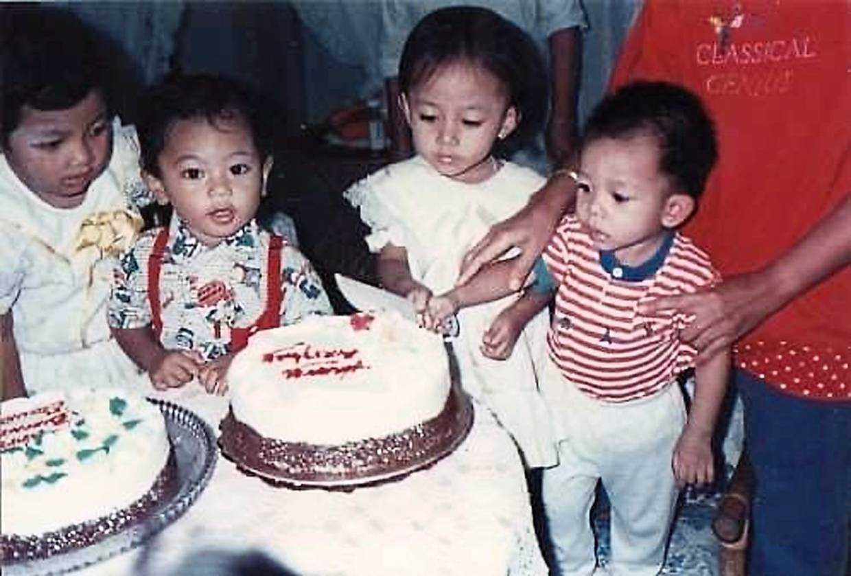 A photo of Nabila when she was three (second from right) sharing her birthday with her younger brother (right).