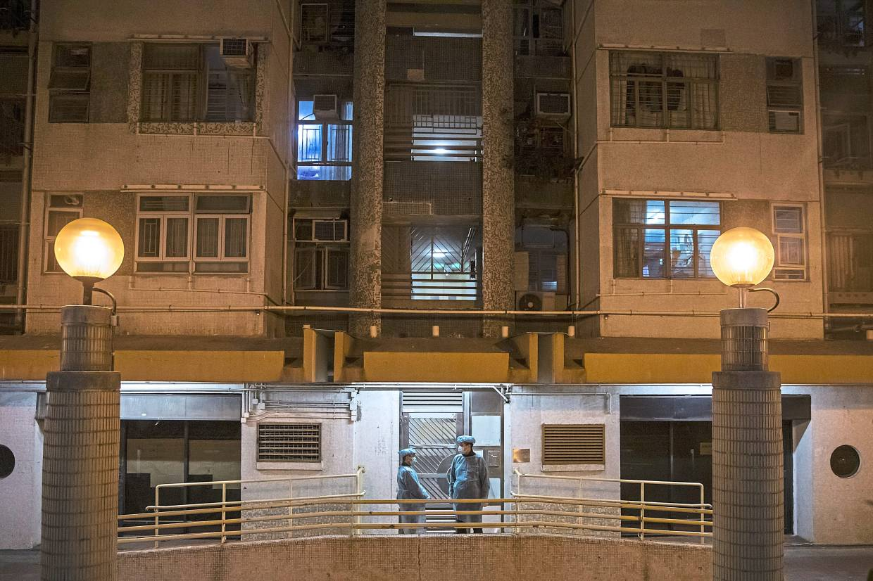Officials with protective gear stand guard outside an entrance to the residential building in Hong Kong on Feb 11, where two residents living floors apart were diagnosed with Covid-19. The virus was suspected to have spread through pipes linking the apartments. — Bloomberg