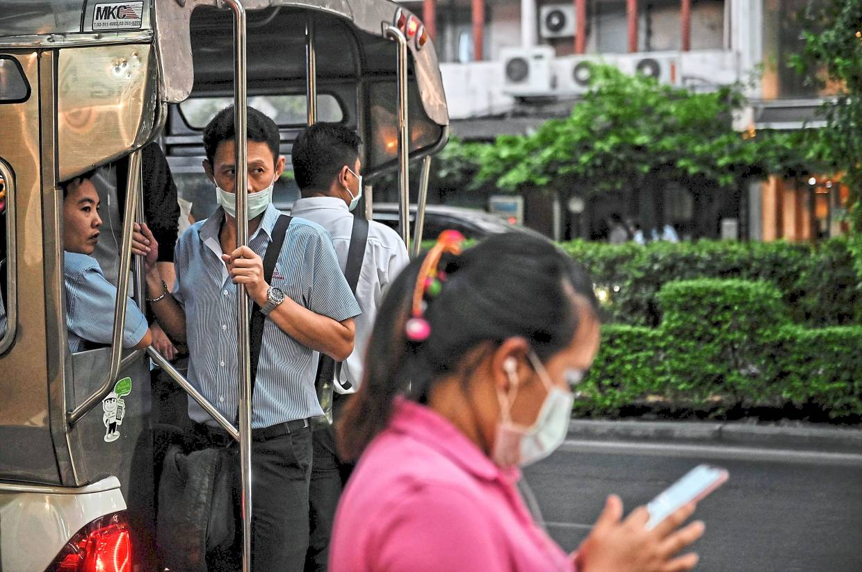 People wear protective facemasks, amid concerns over the Covid-19 coronavirus outbreak, on public transport during the evening commute in Bangkok. - AFP