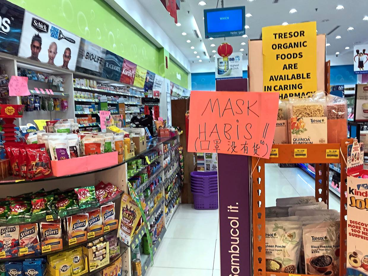 A sign showing face masks are out of stock at a pharmacy. — Photos: RONNIE CHIN/The Star