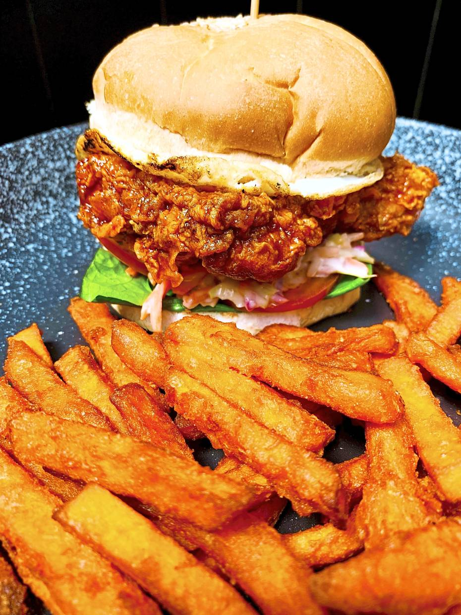 Korean Fried Chicken Burger with fried egg, coleslaw and sweet potato fries.