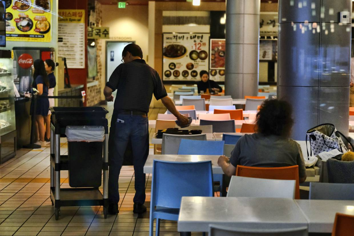 A worker cleans a table at a food court in the Koreatown section of Los Angeles.