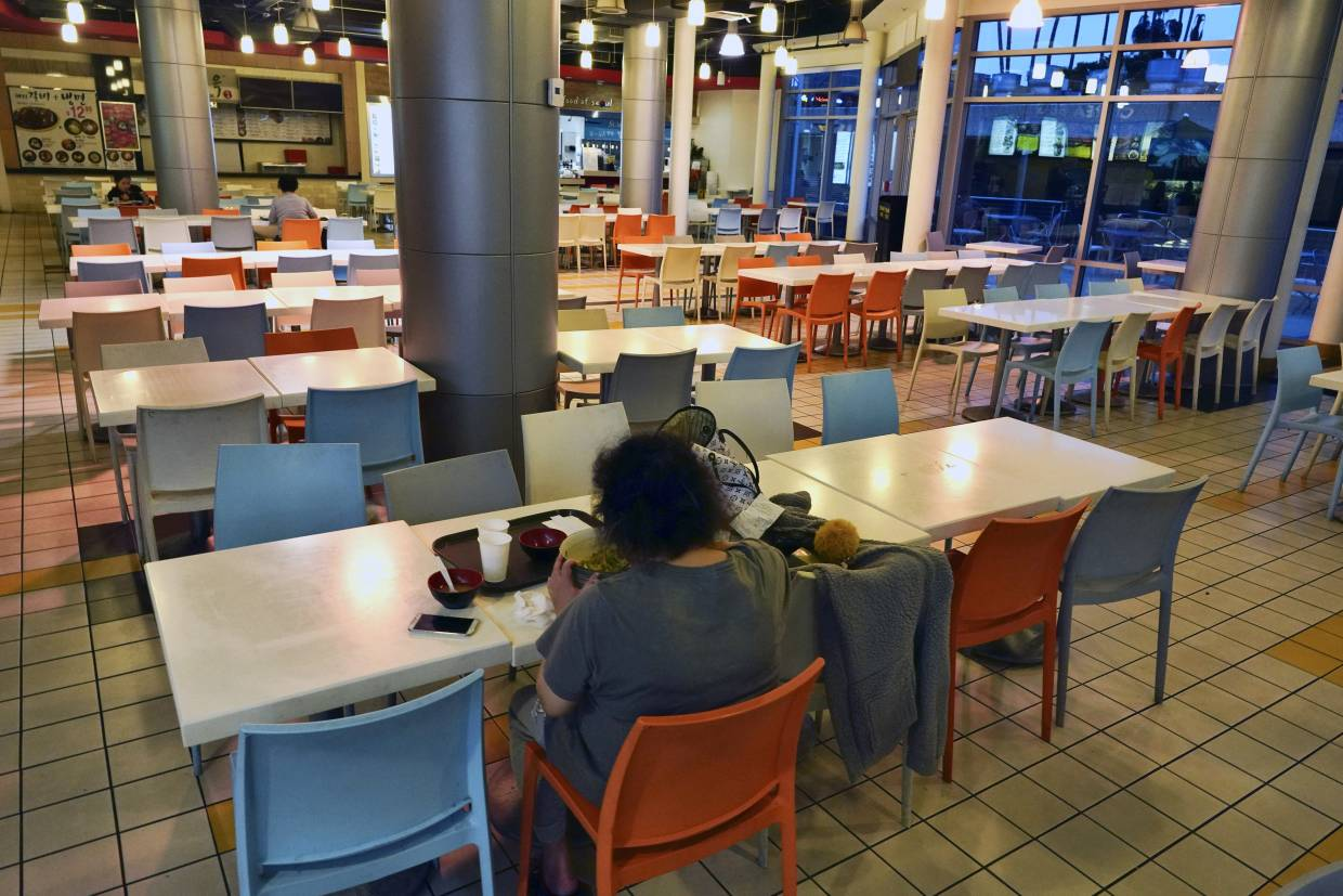 A customer eats a bowl of soup at a deserted food court in the Koreatown section of Los Angeles.