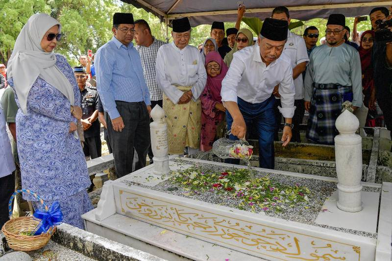 Tan Sri Muhyiddin Yassin pouring scented water on his parents' grave at Tanah Perkuburan Islam Bakri Batu 1, as his wife Puan Sri Noorainee Abdul Rahman (left) watches on.