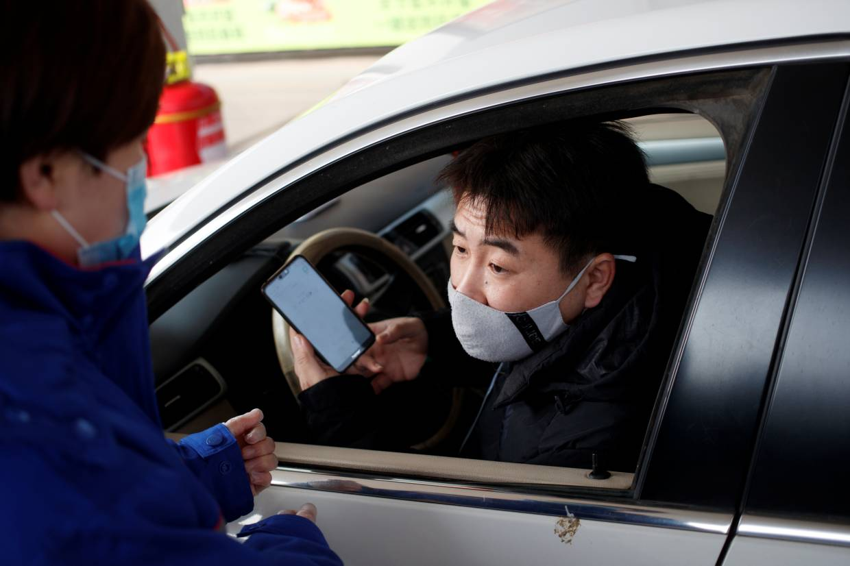 A customer uses an app to order groceries at a Sinopec gas station where customers can buy supplies while they refuel as the country is hit by an outbreak of the novel coronavirus, in Beijing, China.