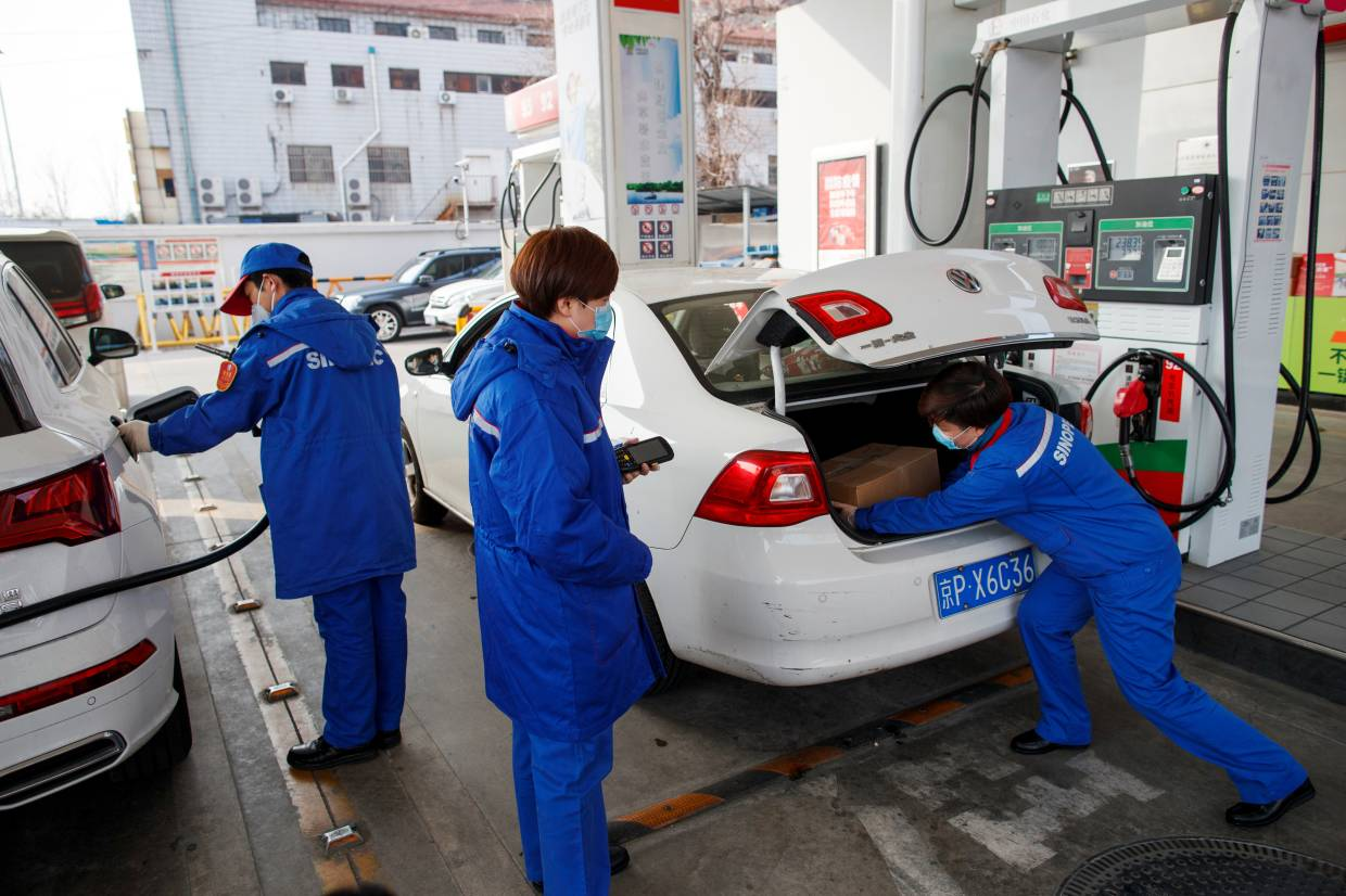 A pump attendant puts a box of groceries into a car at a Sinopec gas station where customers can buy supplies while they refuel as the country is hit by an outbreak of the novel coronavirus, in Beijing, China.