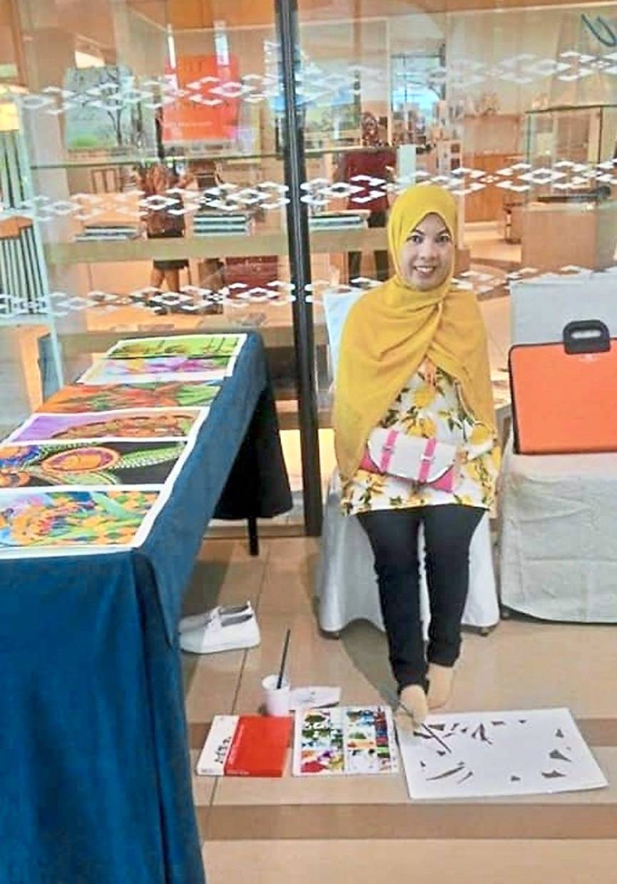 Her feet are the means by which Siti Aishah Yaakob does her batik canting work.