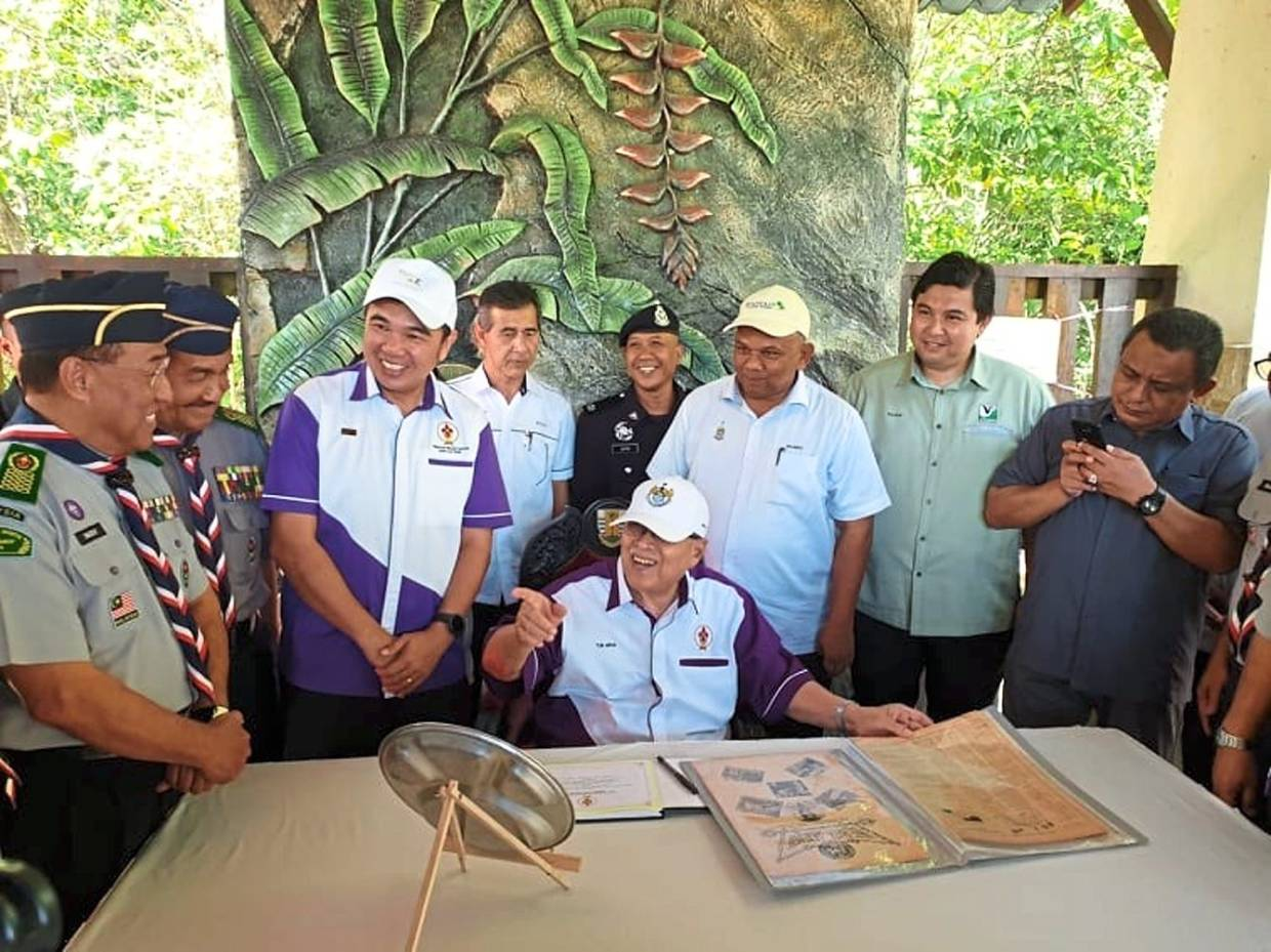 Abdul Rahman sharing a light moment while looking at a collection of photos of past Scouts during a visit to the Penang National Park.