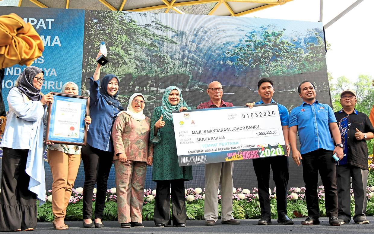 (From fourth left) Rotina, Rosida and Nor Hisham presenting the first prize to Johor Baru City Council for the Most Beautiful Park National Initiative.