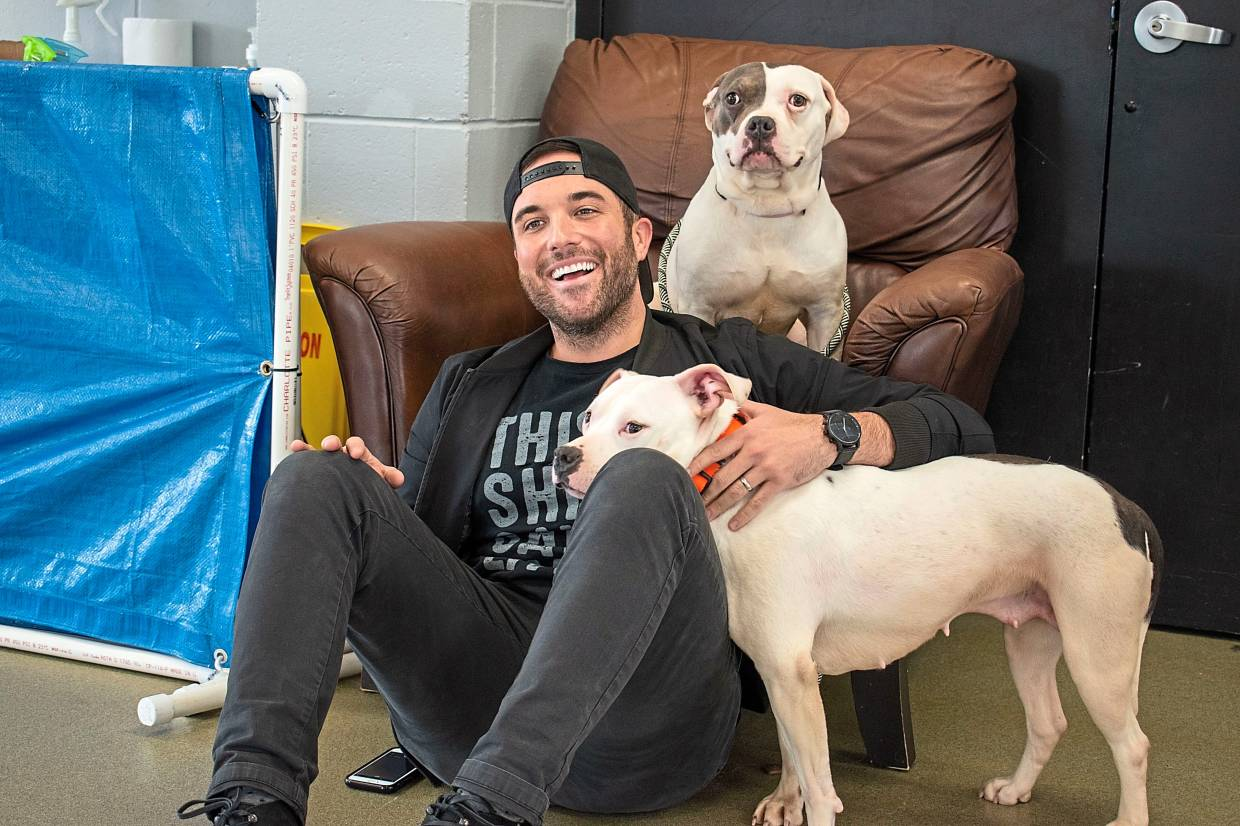 Laughing as he poses with sisters Grace and Frankie at the animal shelter. Rich's visit to the shelter is to raise awareness that dogs are in need of adoption.