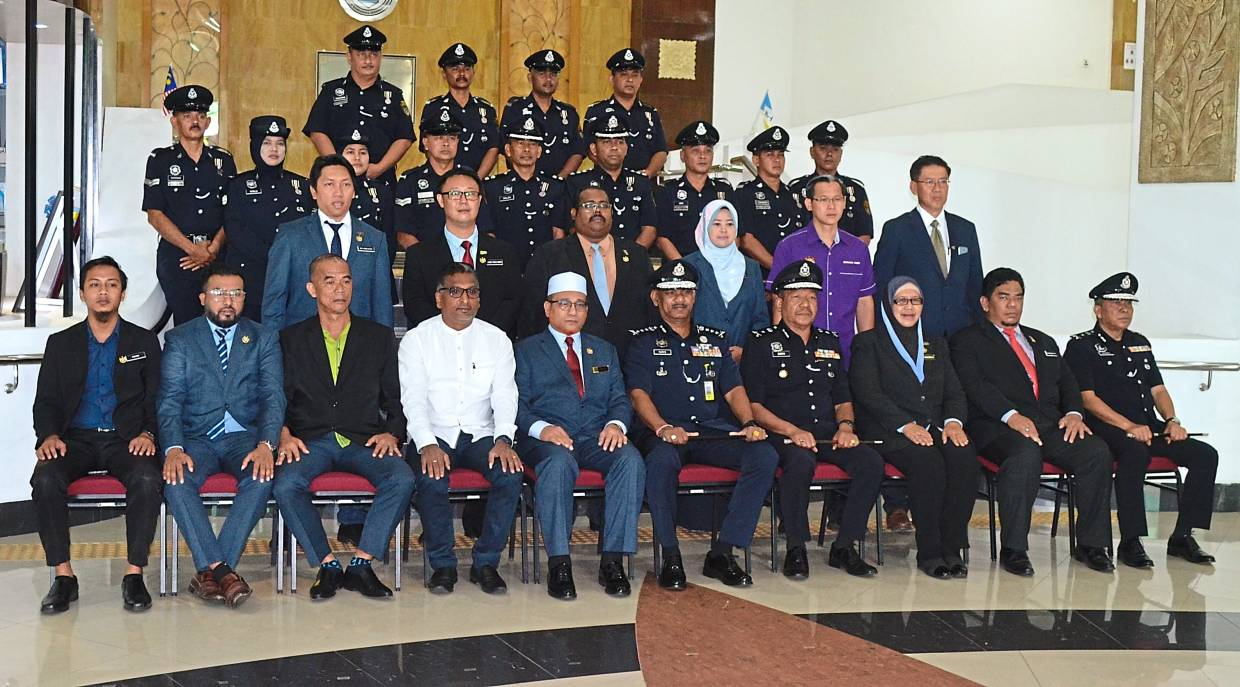 Former Comm Narenasagaran (seated, sixth from left), Rozali (white songkok), MBSP councillors and senior police officers having a group picture with recipients of the Pingat Kebaktian.