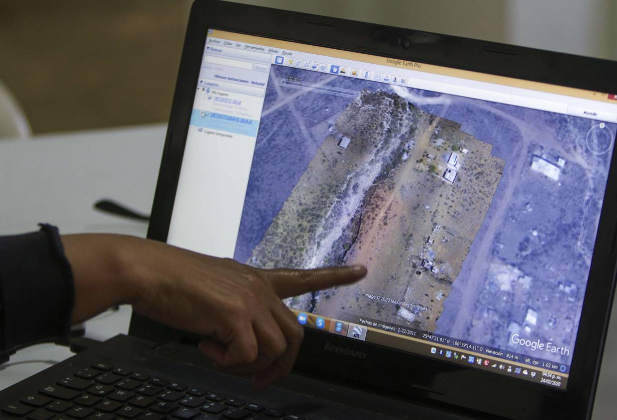 FUNDENL members showing pictures taken with a drone, comparing the differences of a same area throughout the years at 'Las Abejas' cooperative land, in the municipality of Salinas Victoria, Nuevo Leon state.